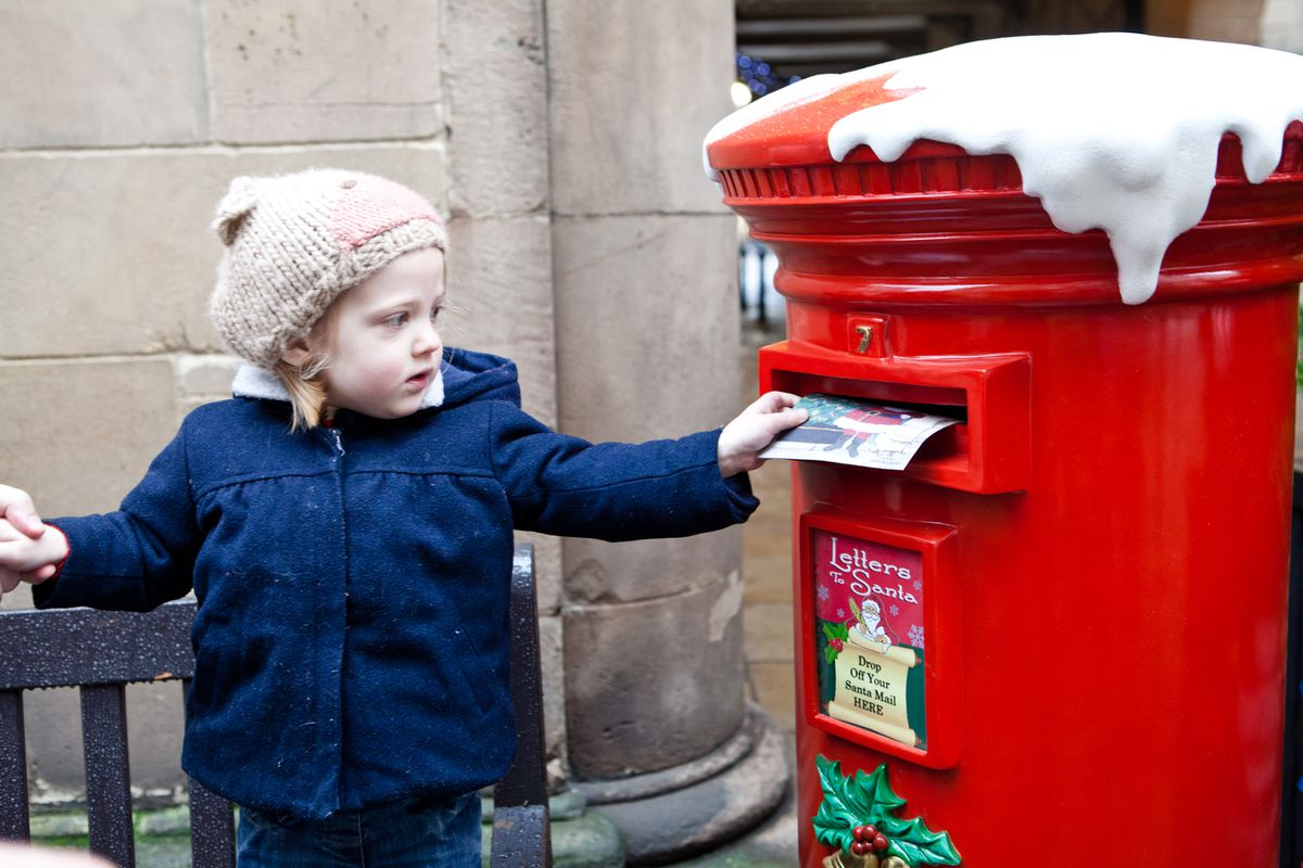 Flora Slater, three, posts a letter to Santa