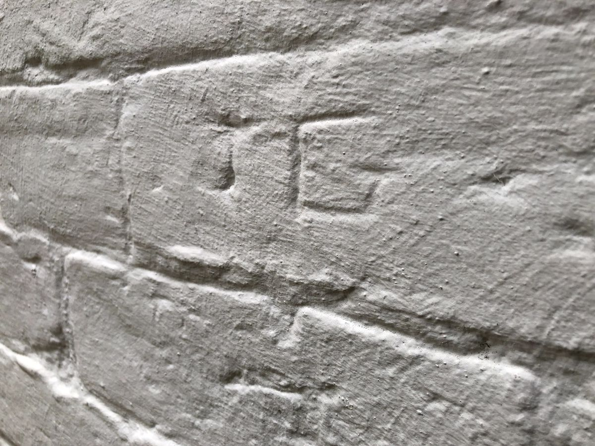 """The mysterious initials """"J G"""" are carved into a wall."""