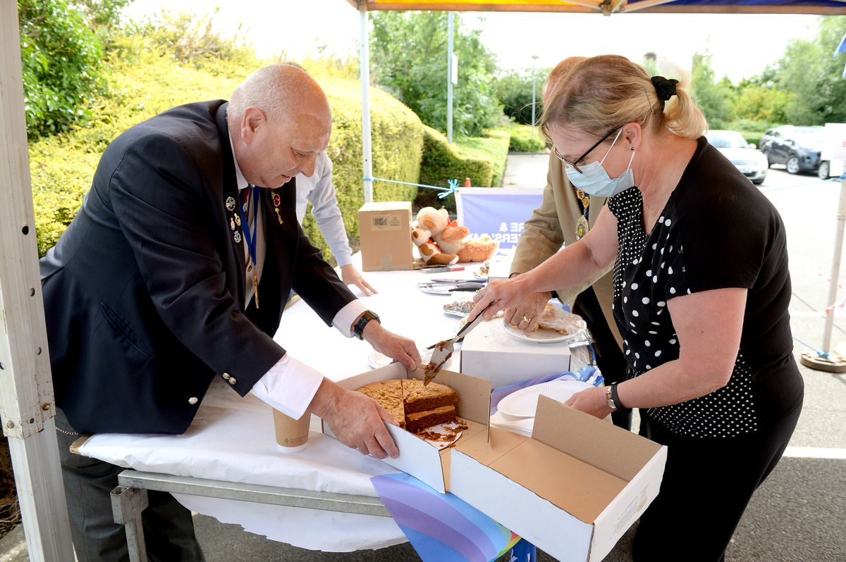 Practice manager Michelle Matthee cuts herself a slice of cake at the NHS day of thanks in Market Drayton