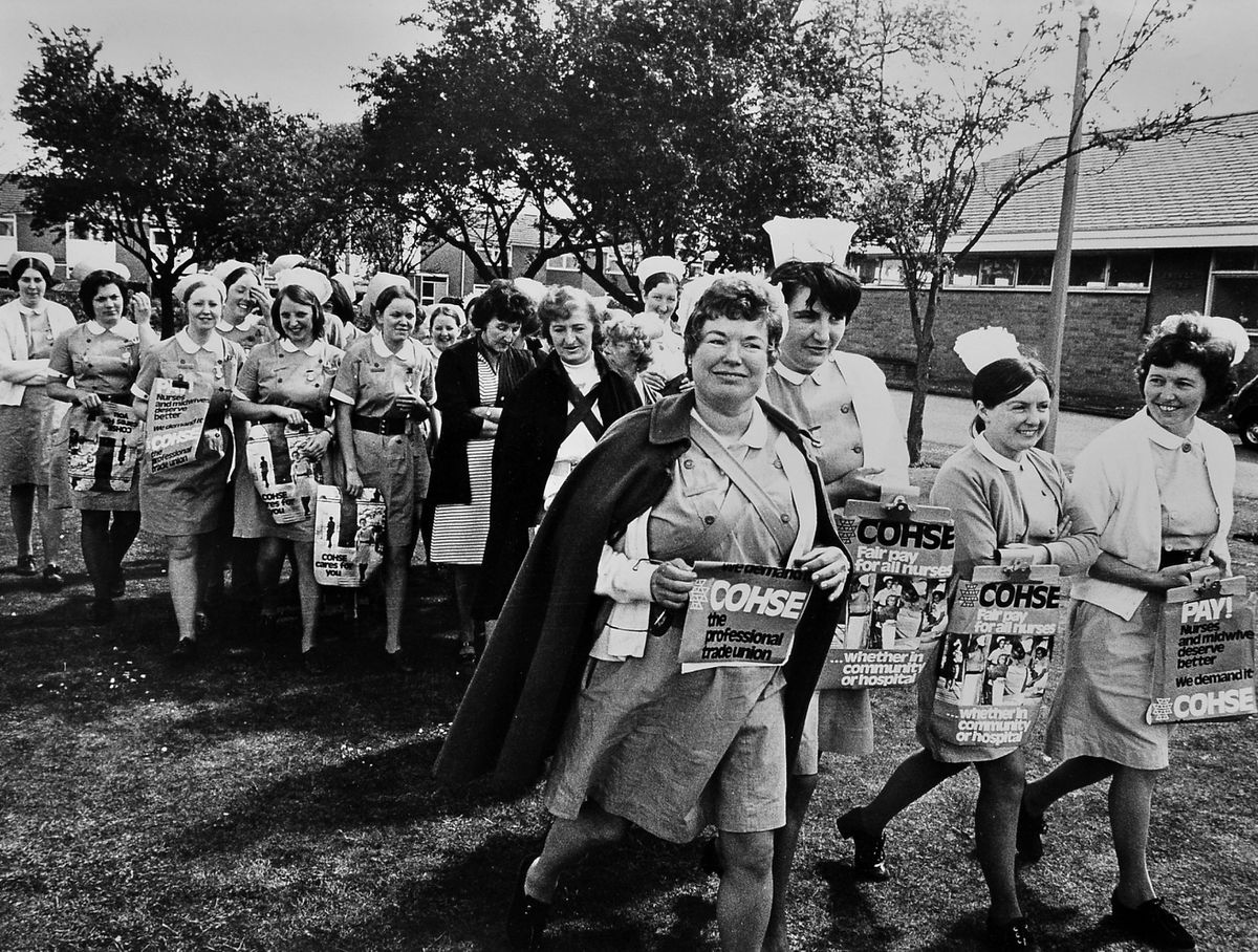 We're on strike! In June 1974 about 30 nurses took part in a one hour token strike at the Shropshire Orthopaedic Hospital, Oswestry. The nurses, members of COHSE, their trade union, spent the hour sitting on a lawn in front of the hospital. The strike was part of a national campaign for better pay.