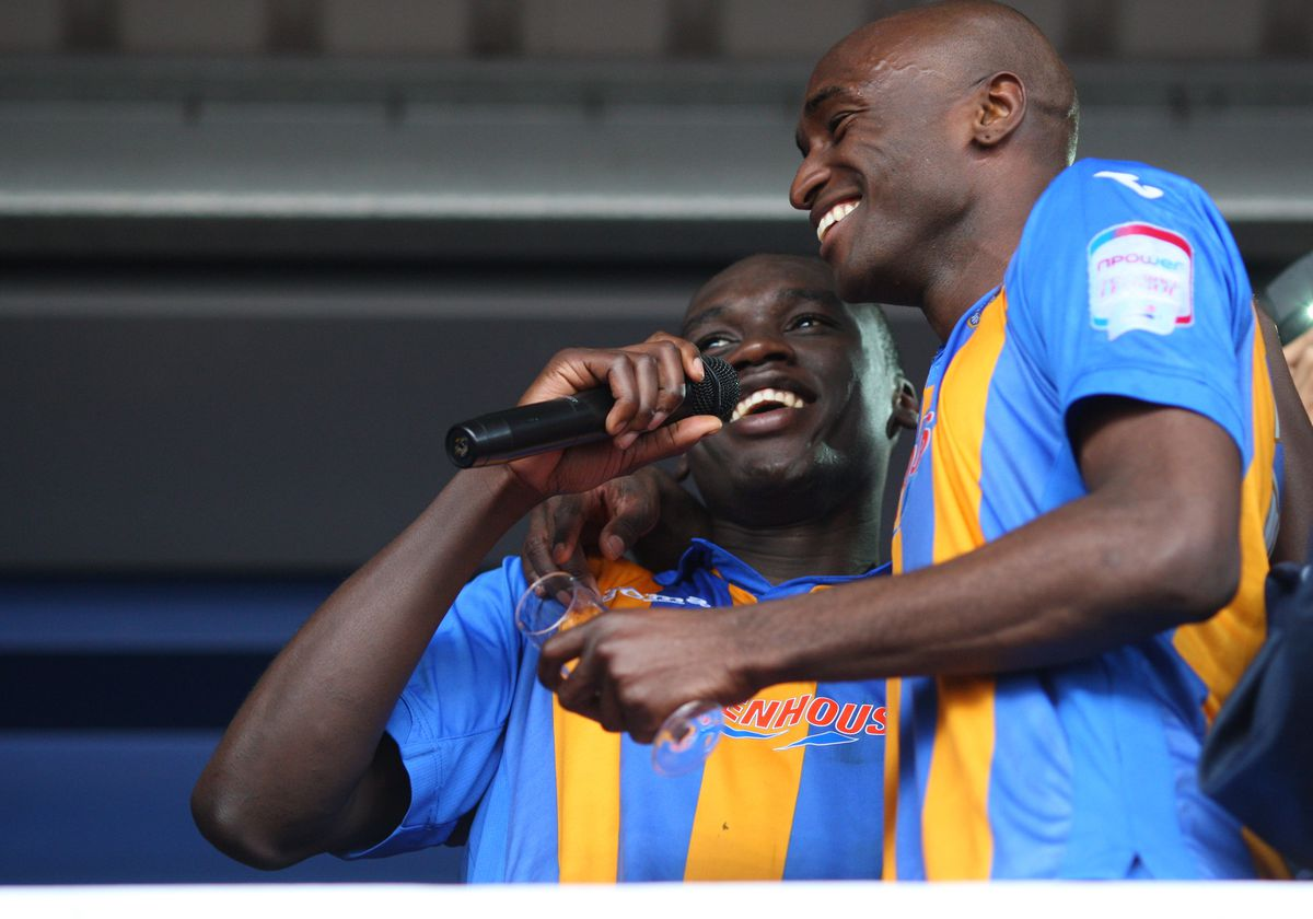Jermaine Grandison of Shrewsbury Town sings a song to the Shrewsbury Town fans as he and Marvin Morgan of Shrewsbury Town celebrate promotion to League One