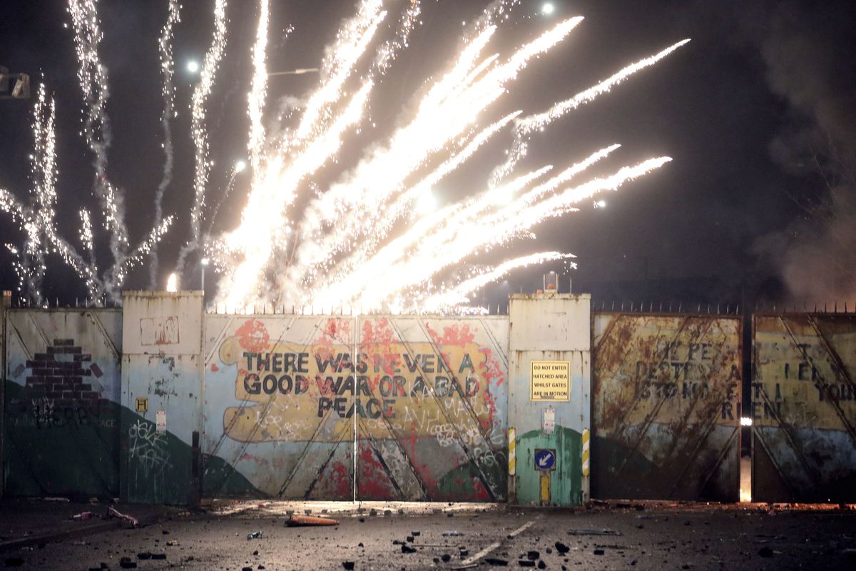 A firework explodes as Nationalists and Loyalists clash with one another in Belfast on Wednesday