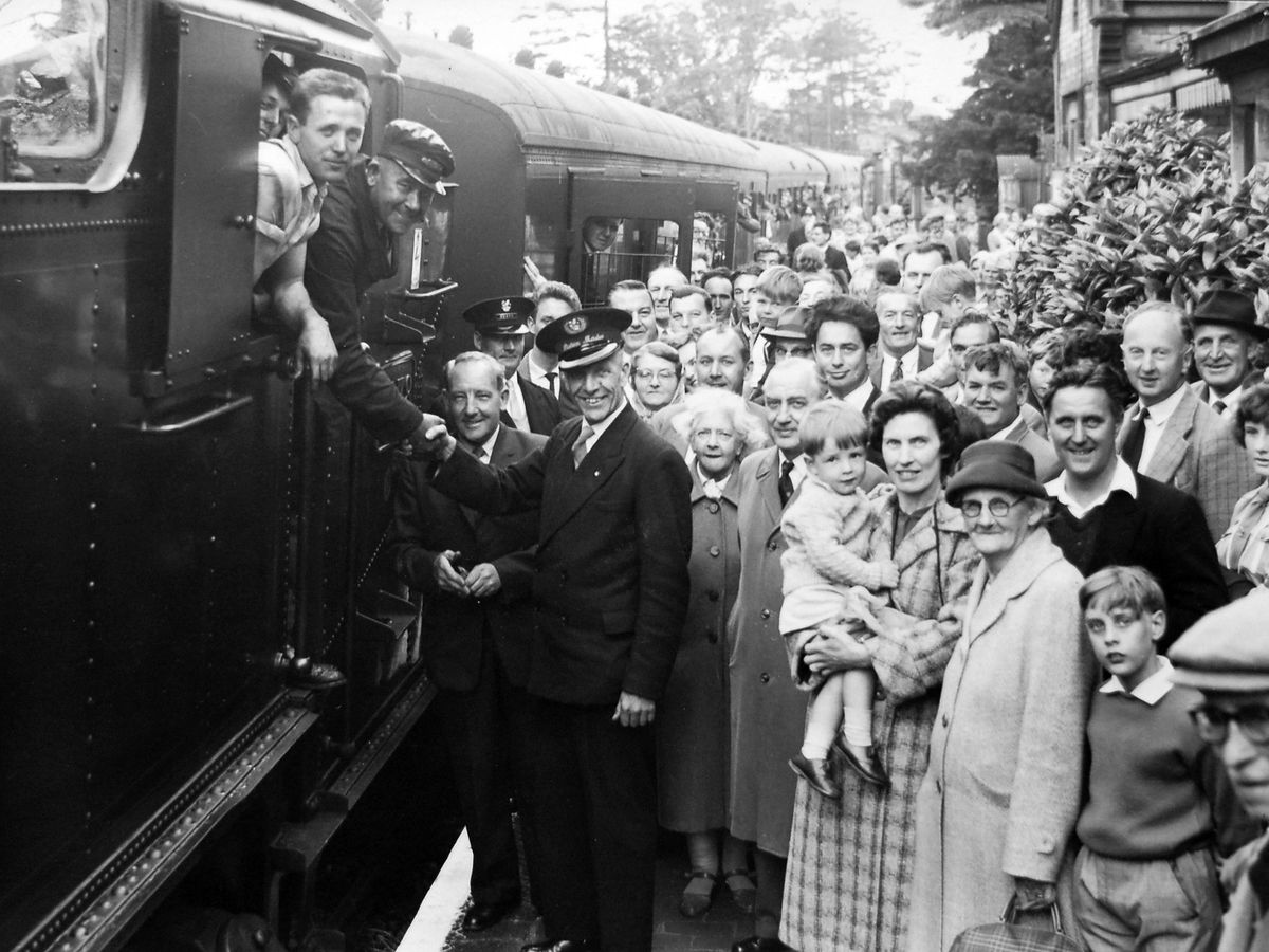 Stationmaster Francis Cole shakes hands with the driver, Jack Darrall, of Wellington, and fireman Terry Thorpe, of Dawley, as the last passenger train prepares to leave Much Wenlock.