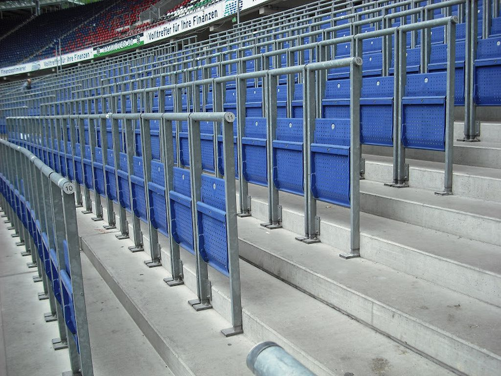 Modern safe-standing areas include railings with fold-down, locking seats