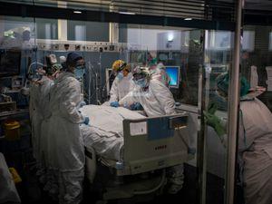 Medics treat a patient in a hospital ICU