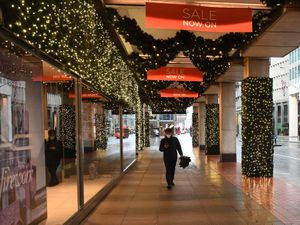 A man walks outside House of Fraser on Victoria Street in Westminster, London.