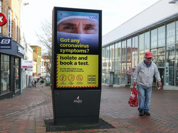 A person walks past a Government coronavirus sign