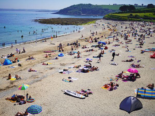 People enjoy the sunshine on Gyllyngvase Beach near Falmouth in Cornwall