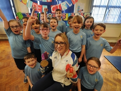Athlete shows off her medals to pupils