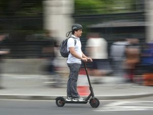 A stock image of a man on an electric scooter
