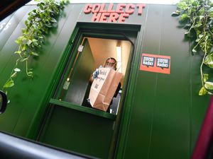 A member of staff hands out a meat-free burger at the new drive-thru in east London