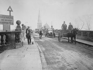 A cow strolls over the old English Bridge in Shrewsbury shortly before the bridge was rebuilt in the 1920s.