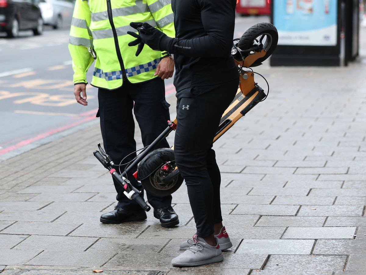 A police officer speaks to an e-scooter rider
