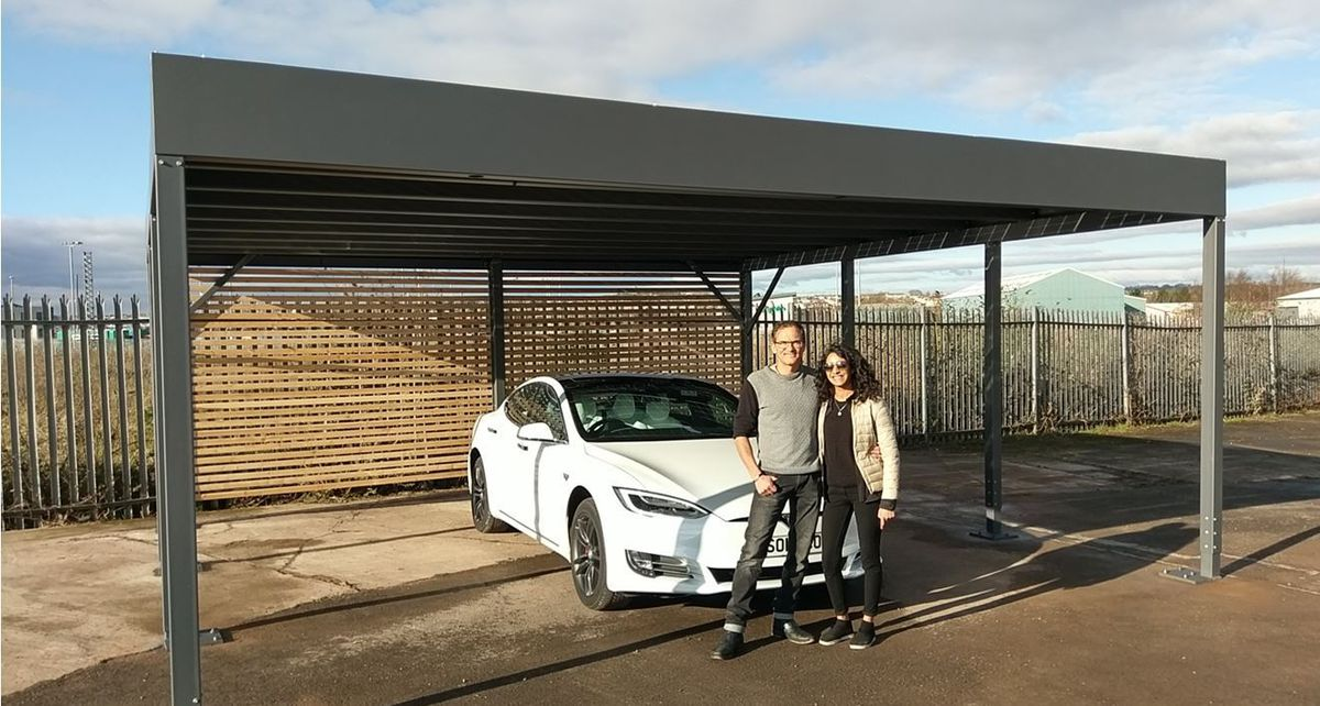 Parveen Begum with business partner Mark Maurice, and one of their solar-powered car ports