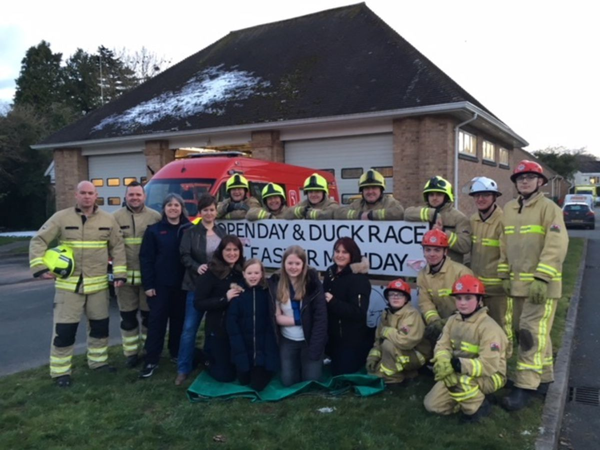 Bethan, her family and firefighters getting ready for the open day and charity duck race.