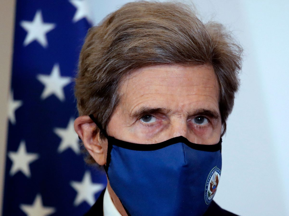 US climate envoy John Kerry wears a blue mask over his nose and mouth