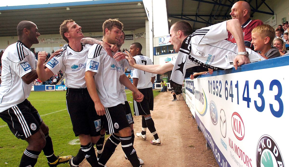 Alex Meechan, second left, celebrates a goal with Phil Trainer, Andy Brown and the Bucks fans. Above right: Getting his hands on play-off silverware