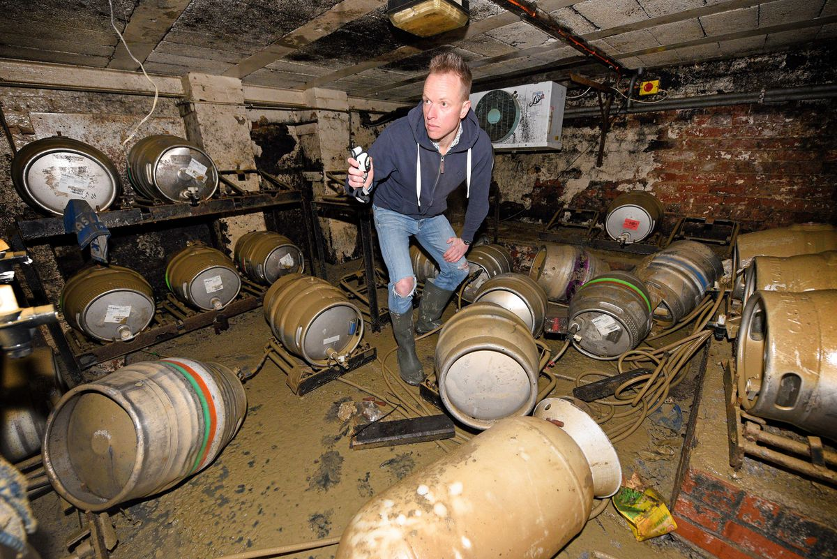 Ollie Parry, owner of The Salopian bar, Shrewsbury, surveys the cellar of the pub after the extensive flooding
