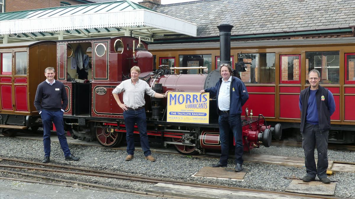 Morris Lubricants' executive chairman Andrew Goddard (second form left) and the company's heritage account manager Keiron Thorogood hold one of the new signs watched by Talyllyn Railway's general manager Stuart Williams (left) and engineering manager Chris Smith (right).