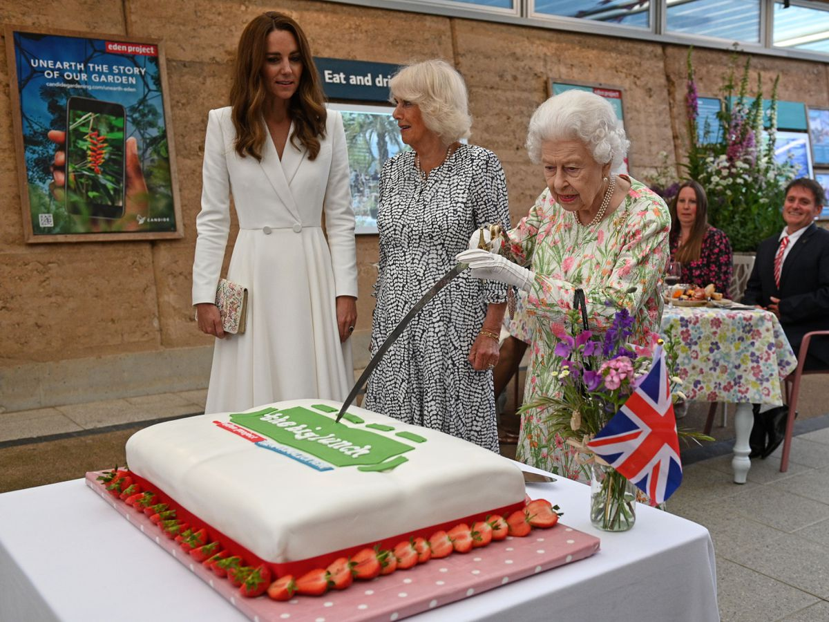 The Duchesses of Cambridge and Cornwall watch as the Queen cuts the cake with a sword