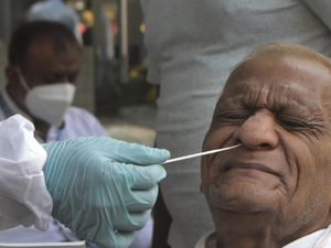 A health worker takes a swab sample to test for Covid-19 on a street in Mumbai, India (Rajanish Kakade/AP)