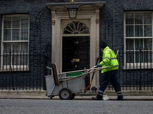 A street sweeper in Downing Street, London, ahead of Prime Minister Boris Johnson's speech to Parliament where he will set out the road map for easing coronavirus restrictions across England