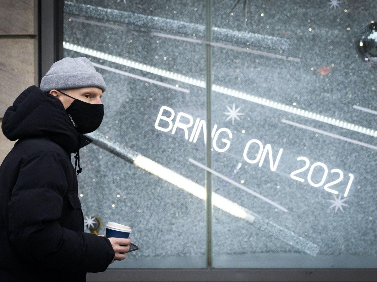 """A shopper wearing a protective face mask walks past a shop sign that read """"Bring On 2021"""" in Edinburgh city centre."""