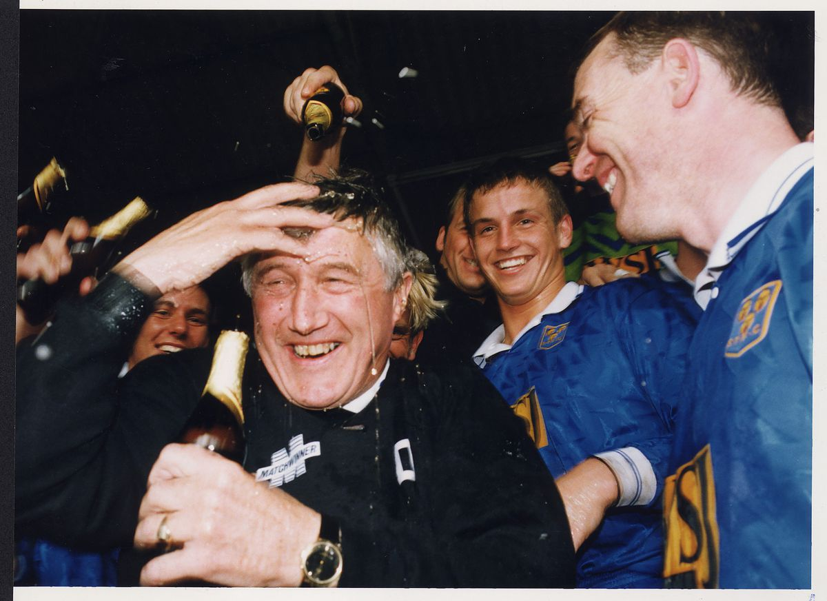 Fred Davies is drenched in beer as his team celebrate promotion in April 1994