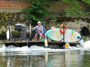 Enjoying a journey down the river in Shrewsbury in the warm weather was this boater with a barbecue and surfboard