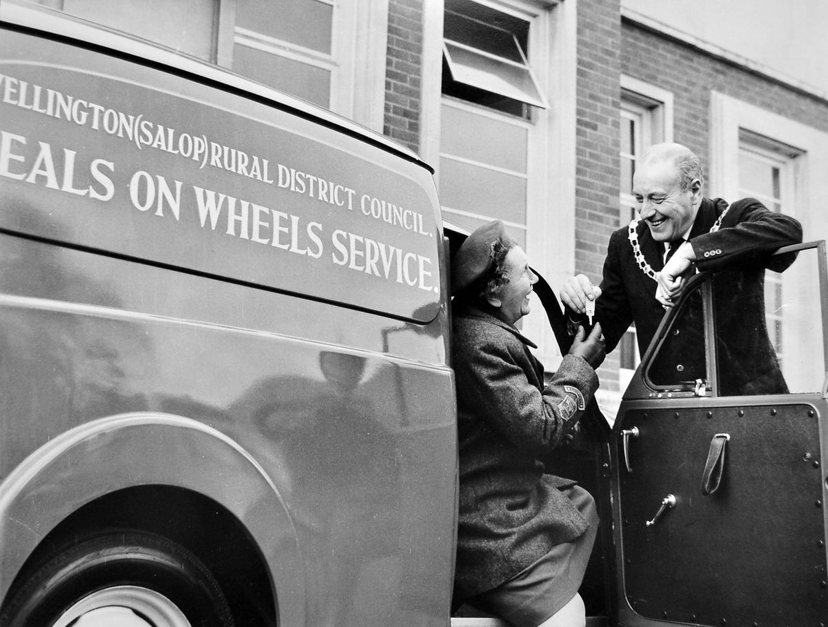 """A new meals on wheels van is handed over to the Women's Voluntary Service at the Wellington Rural District Council offices on February 11, 1965. According to the original caption """"Mrs Martin Wilson (sic – back then it was common to refer to women by the husband's name), county WVS organiser, complete for the road takes charge of their new meal on wheels vehicle presented to them from Wellington RDC by chairman Councillor Isaiah Jones."""""""