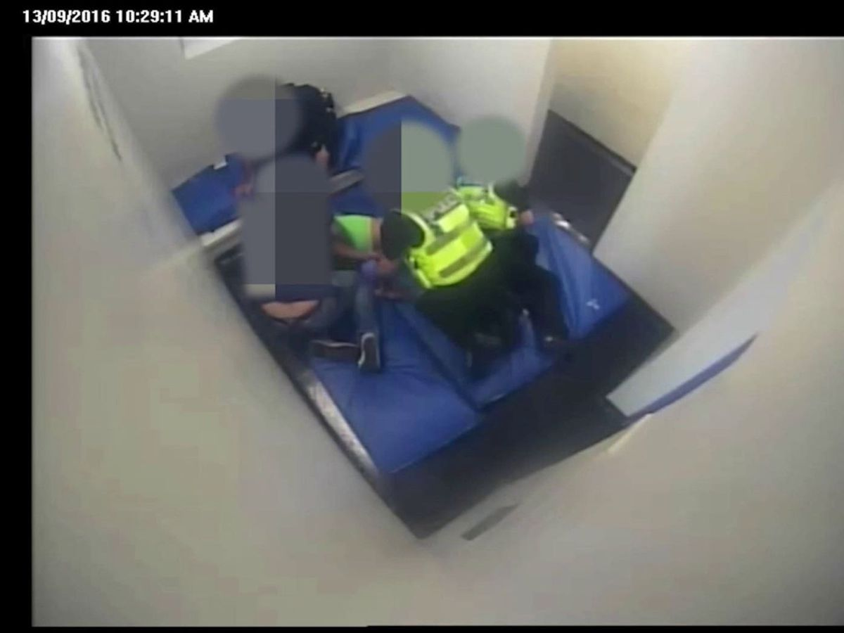 Andrew Hall being restrained