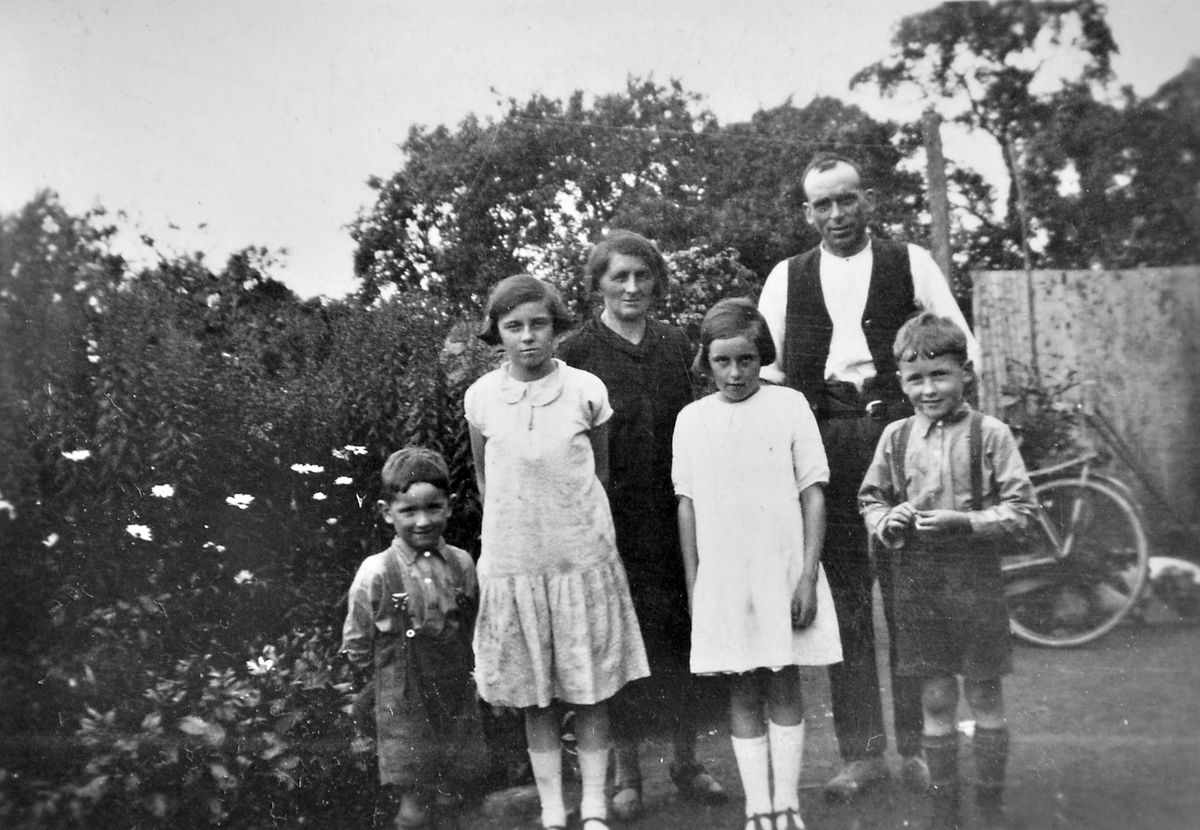 A very young Norman Jones with the rest of his family. He thinks the picture was taken at either Wollerton or Prees. From left are himself, Norman Jones, sister Olive Jones, mother Elizabeth Jones, sister Doris Jones, father Harry Jones, and brother, also called Harry Jones. Norman says Olive married aged 17 or 18 at the beginning of the war. Her married name was also Jones. Doris married a Joe Lister.