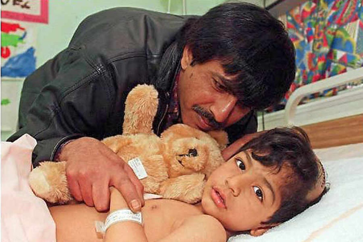 Ahmed Malik, three, with his father Javed Pervaz in hospital