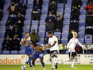 Shrewsbury Town fans watches the action from inside the stadium