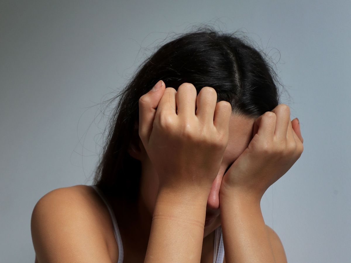 A teenage girl with her head in her hands