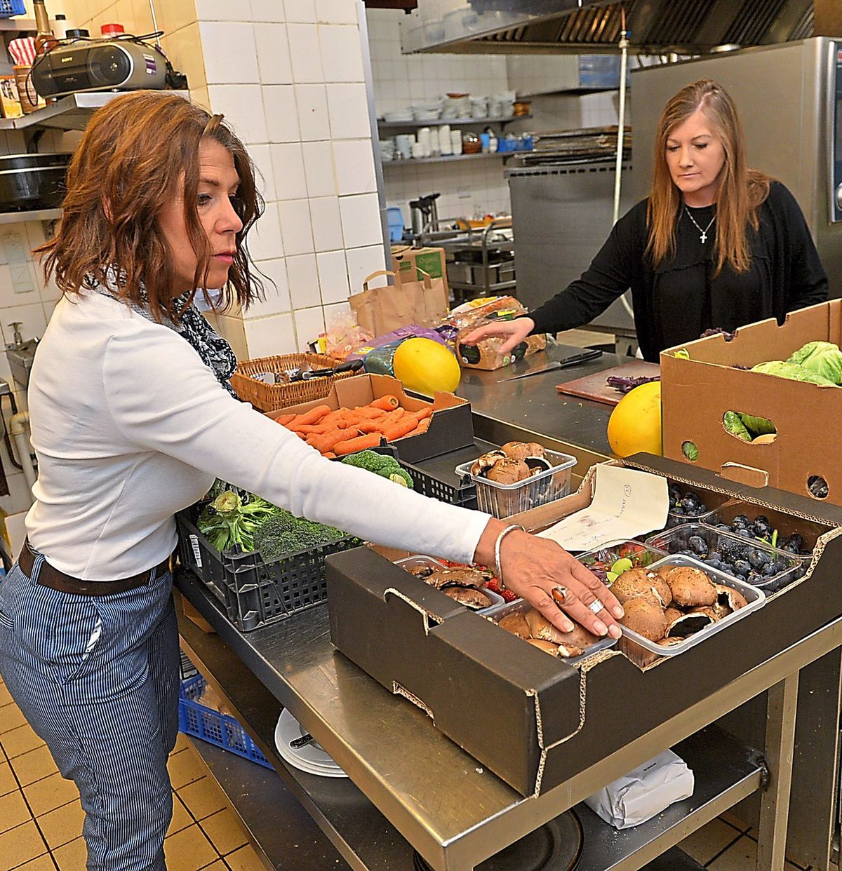 Charlie Green, left, and Jacki Law prepare supper