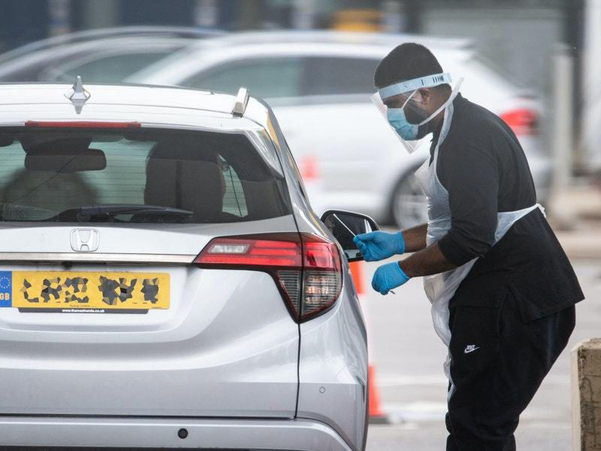A tester wearing PPE holds a swab at a drive-through site