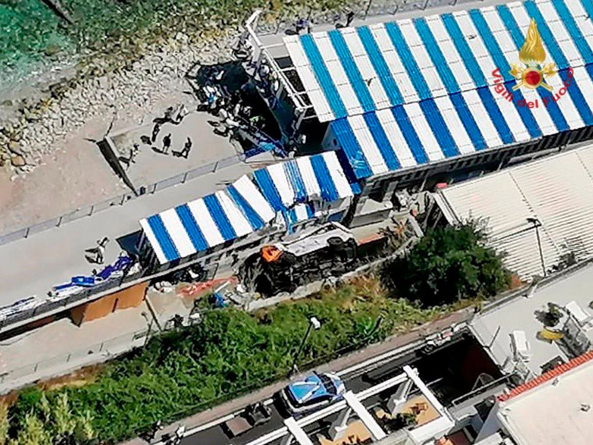 A bus lies on its side after crashing through a guardrail on Capri