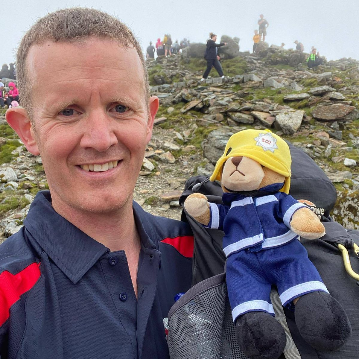 Dave Latham at the summit with a mascot