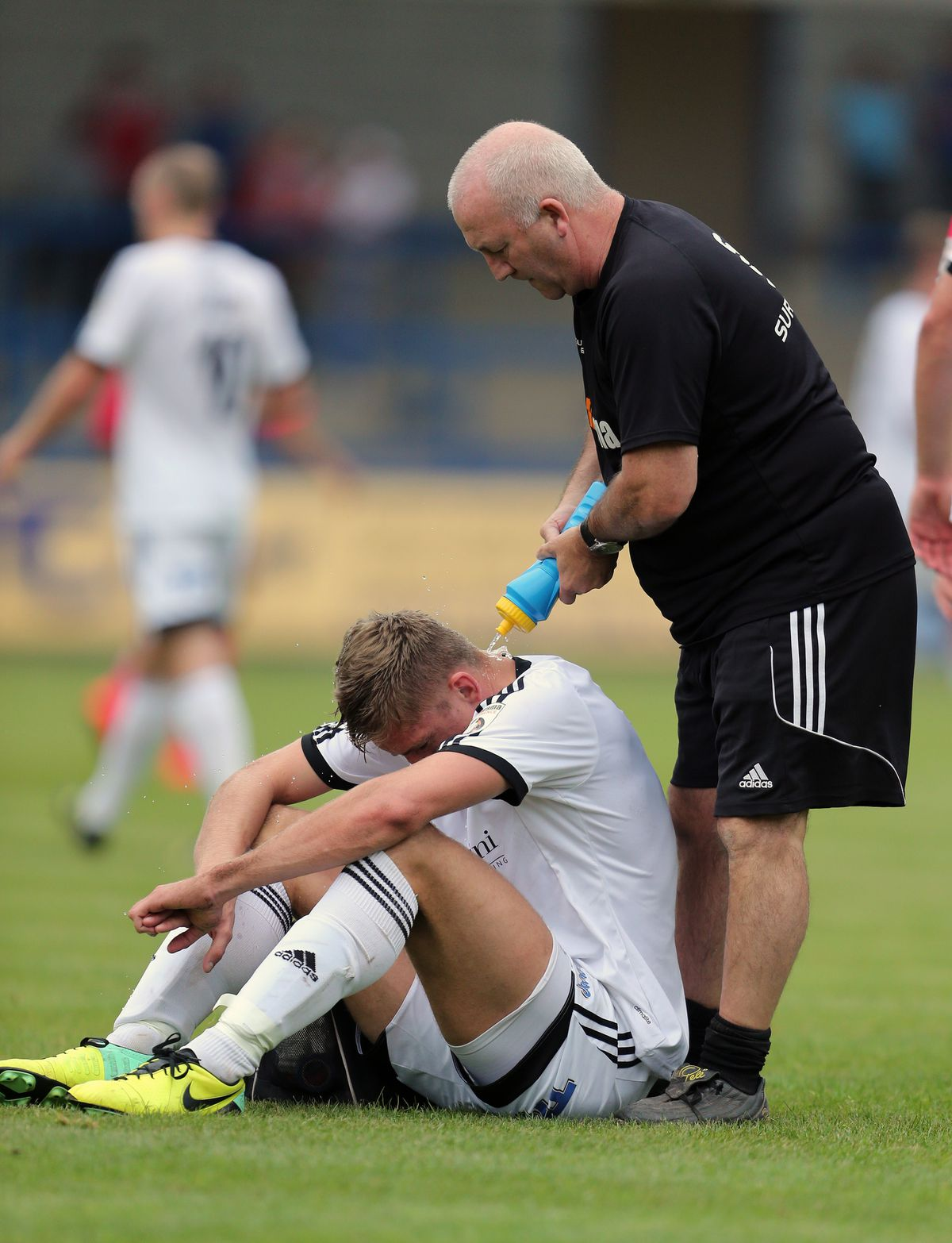 Mike Phenix of AFC Telford United receives treatment from Telford physic Chris Roberts .