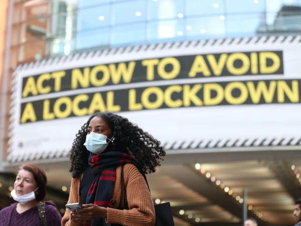 A woman wearing a face mask walks through Manchester (Martin Rickett/PA)