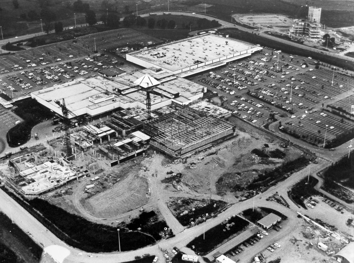 A big extension takes shape at Telford shopping centre in the late 1970s. Judging by the state of progress on the landmark Darby House office block, top right corner, which was completed around the spring of 1980, this picture probably dates from 1979. The shopping centre had originally opened in October 1973. The first big shops were the Carrefour hypermarket, which is upper right and going by the number of cars in the car park is having a busy day, and Sainsbury's, which is left of centre.