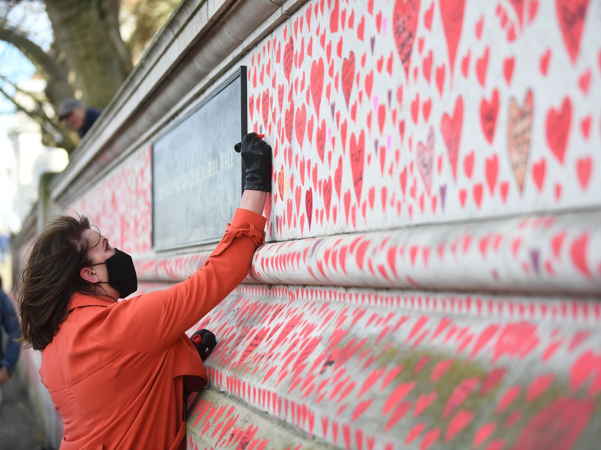 A woman paints hearts on to the National Covid Memorial Wall in London