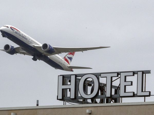 A plane flies over a 'Hotel' sign