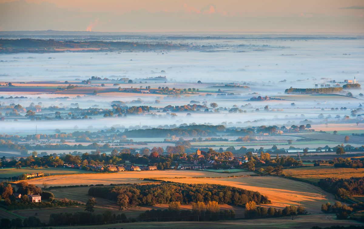 Autumn mist rolls across the Shropshire landscape beyond the village of Wrockwardine, seen from the summit of the Wrekin.
