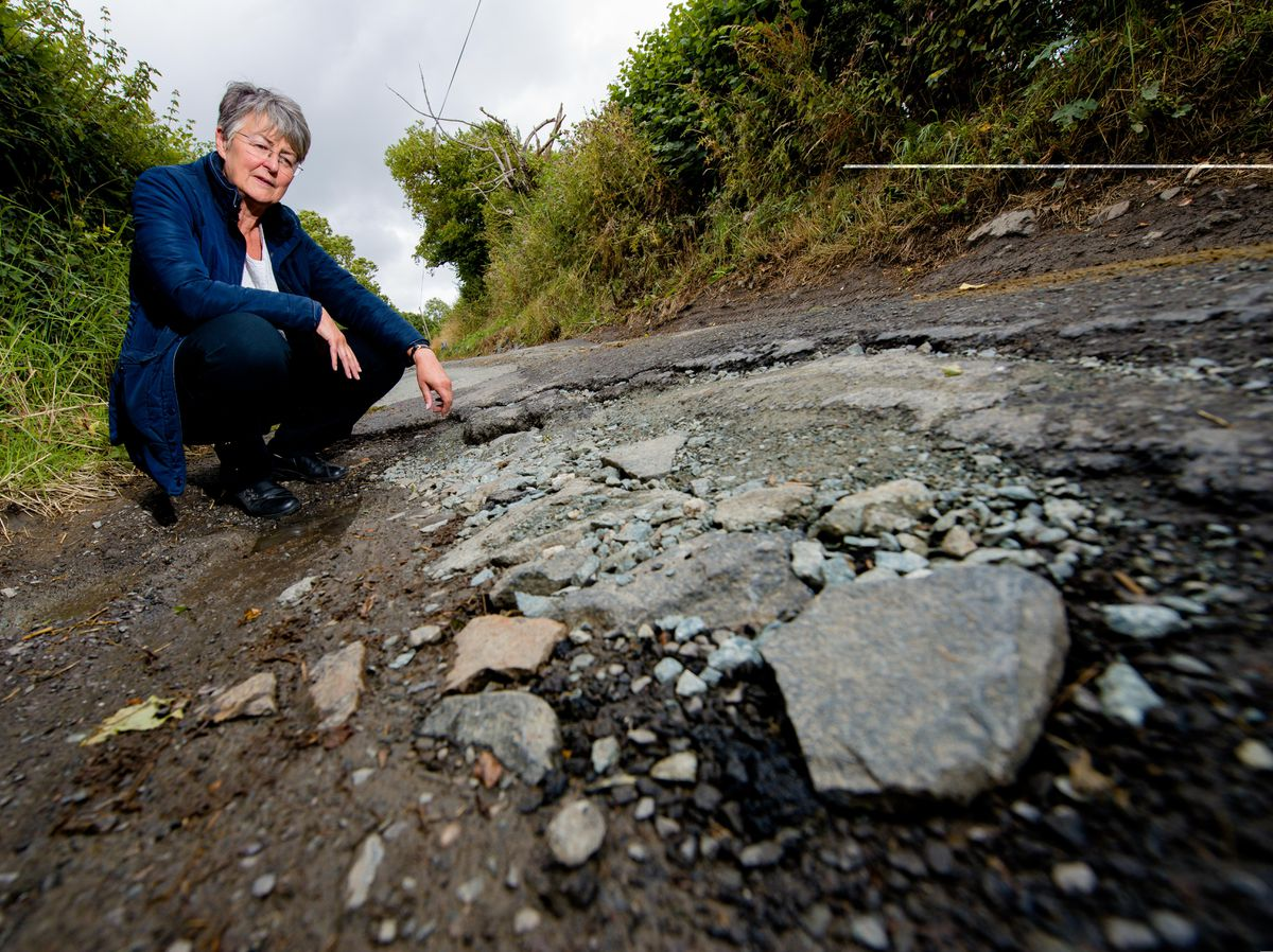 Councillor Heath Kidd examines a pothole in Priest Weston on the Shropshire/Wales border