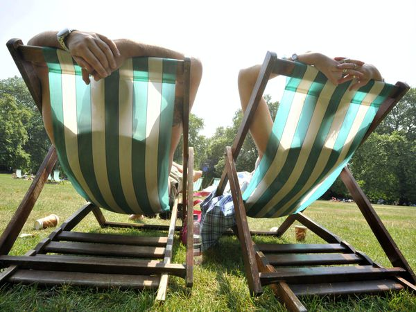 People soak up the sun on the deckchairs in central London's St James's Park