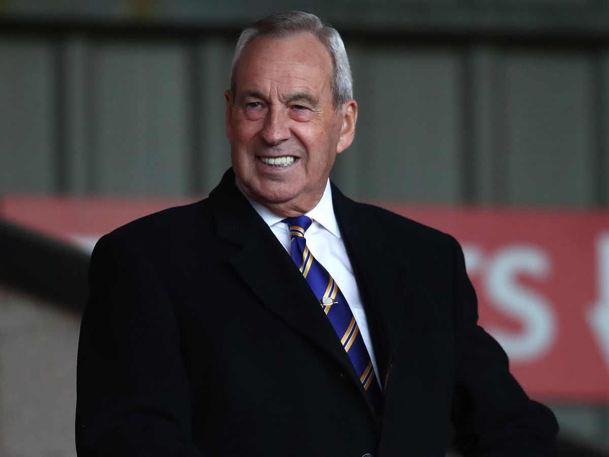 Roland Wycherley, the Shrewsbury Town Chairman watches the match from the away supporters seats at the Banks's Stadium .