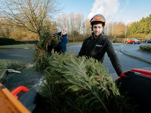 Chris Powell from Chirk and Paul Reese,  chipping people's Christmas Trees. The money he makes will go to the Alder hey Hospital Liverpool. Pictured here outside of Chirk Community Care Home..