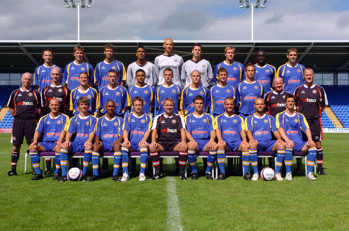 The men who carry Shrewsbury Town's hopes for the new season line up at this week's Prostar Stadium photo call, back from left: Marc Pugh, Grant Holt, Michael Symes, Jasbir Singh, Scott Bevan, Glyn Garner, Kelvin Langmead, Guy Madjo, Richard Walker; middle: Pete Downward (kit man), Nathan Ring (physio), Paul Murray, Kevin McIntyre, James Meredith, Steven Leslie, Marc Tierney, Darren Moss, Dave Hibbert, John McMahon (assistant manager), Stuart Delaney (coach); front: Ben Herd, Stephen Hindmarch, Chris Humphrey, Ben Davies, Paul Simpson (manager), Mike Jackson, Neil Ashton, David Hunt, Shane Cansdell-Sherriff. Picture by: Mark Booth.